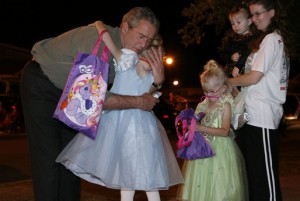 President George W. Bush hugging a trick-or-treater.